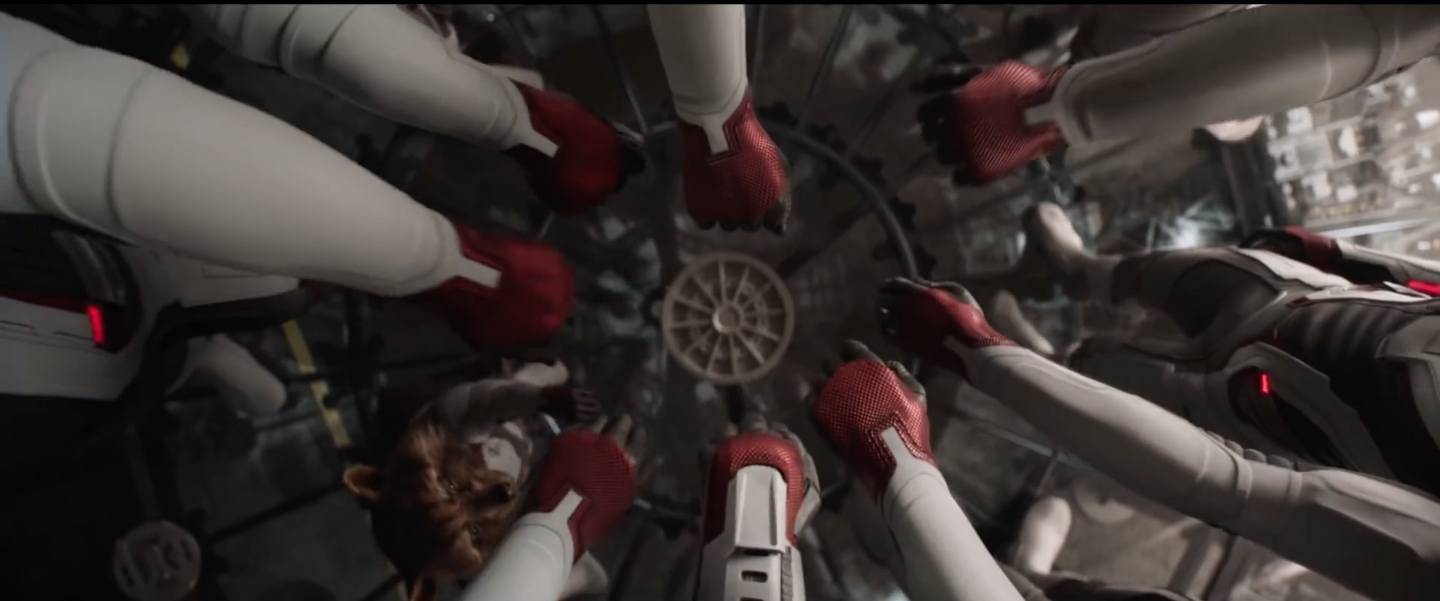 Overhead shot of all of the Avengers with their hands in, ready for the mission